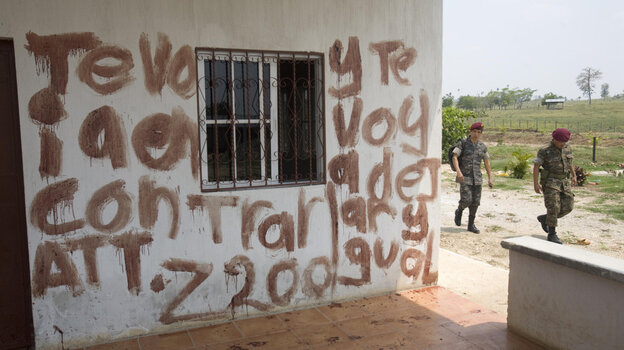 Soldiers walk past part of a message written in blood at the site of a massacre at a ranch in northern Guatemala on May 16. The message is a warning to Otto Salguero — the owner of the ranch, according to local media. Guatemalan authorities blame the killings on the Mexican drug cartel Los Zetas.