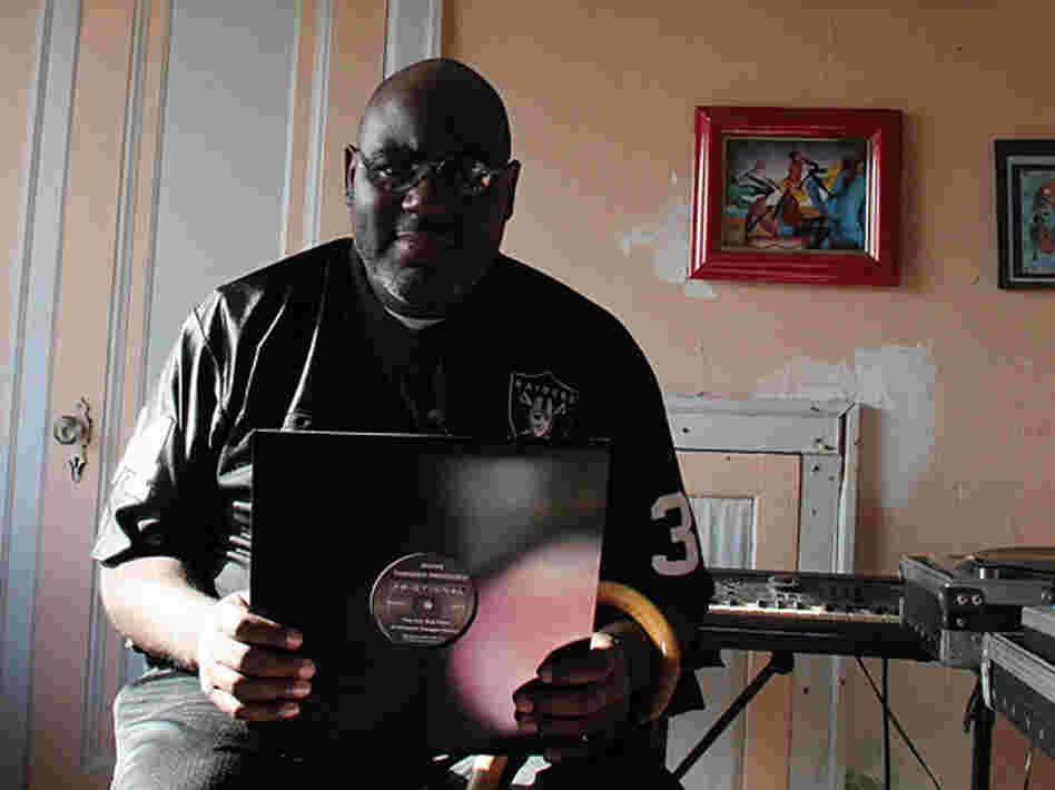 "Anthony ""Shake"" Shakir in his home, holding up one of his records."