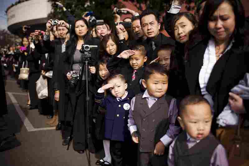 Thousands from the Hmong community line the streets as the general's body is transported on a horse-drawn carriage to Fresno's convention center for the funeral.