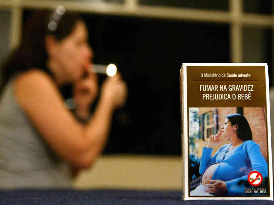 "A Brazilian cigarette pack shows a pregnant smoker with the caption ""The Ministry of Health warns: smoking during pregnancy is detrimental to child's health,"" while a woman lights a cigarette in the background."