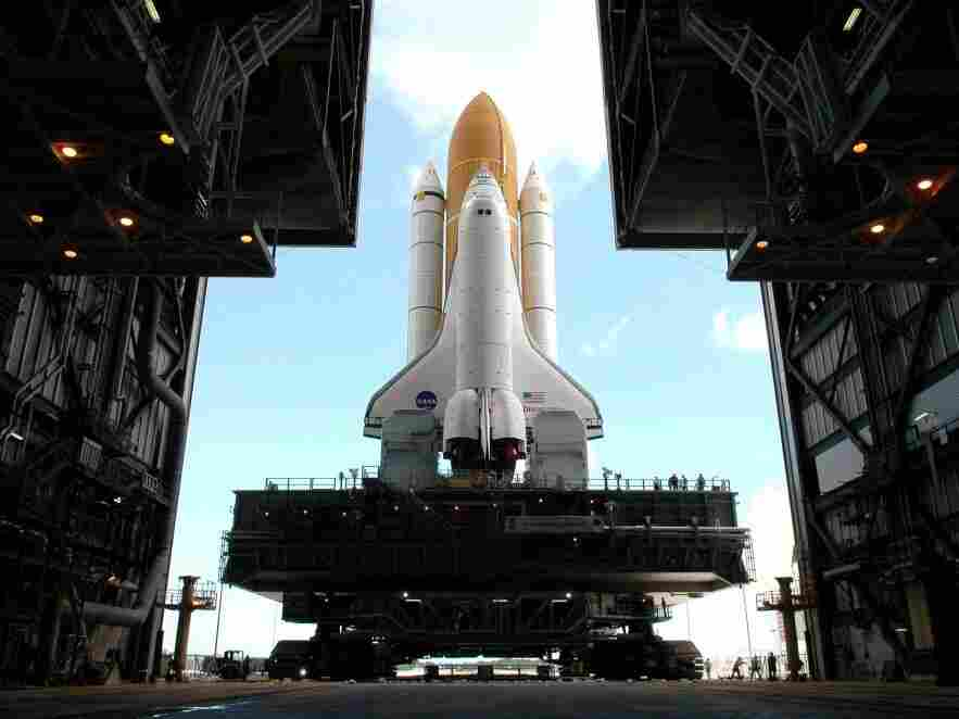 Framed in the doors of the Kennedy Center's Vehicle Assembly Building, the crawler begins the long journey toward Launch Pad 37B with space shuttle Discovery in April 2005.  This enormous cross between a tank and a cargo ship is the largest self-powered land vehicle in the world.