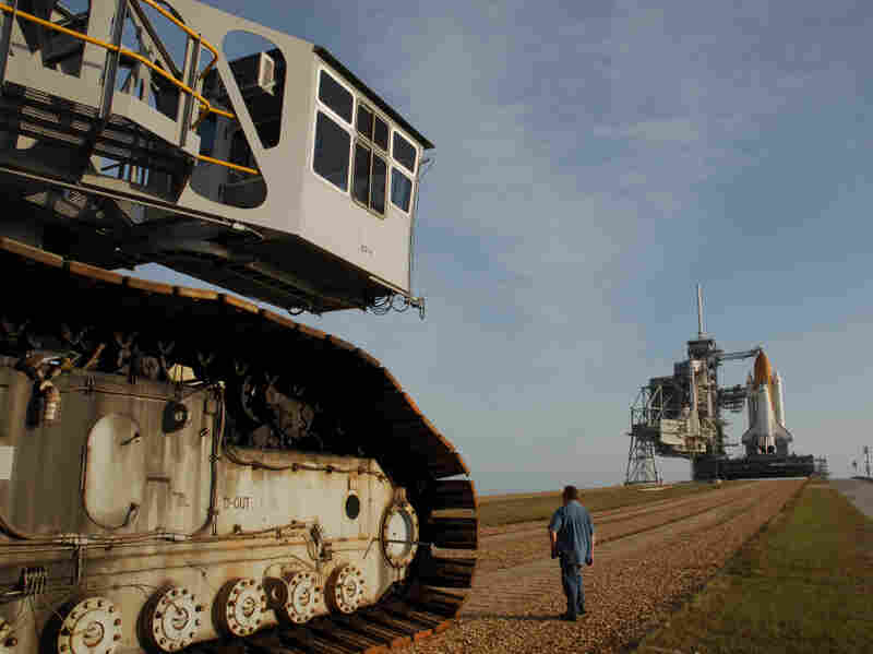 """The crawler's titanic treads grip the dirt of the """"crawlerway,"""" a special road between the launchpad and the hangar-like structure where the shuttle is assembled.  The road is designed to hold the combined 18 million pounds of the crawler and the shuttle it carries."""