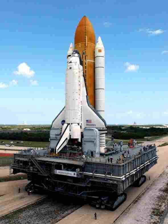 The crawler inches toward Launch Pad 39B at the Kennedy Space Center in 2005, traveling 1 mph and burning a gallon of gas every 32 feet. In 2005, its precious cargo was space shuttle Discovery; for its last trip at the end of May, the crawler will transport space shuttle Atlantis to its final launch.