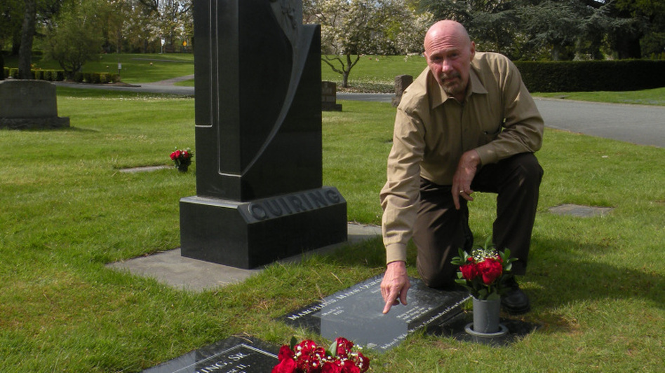 Dave Quiring Jr. inherited Quiring Monuments from his father 43 years ago. He points to the QR codes he has attached to the gravestones of his father and mother at their family plot in Seattle's Evergreen Washelli Memorial Park.