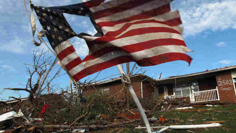 A torn U.S. flag hangs outside a house damaged during Sunday's massive tornado in Joplin, Mo. As of Thursday, local police said they had arrested 16 people for looting and burglary and four for assault since the twister hit.