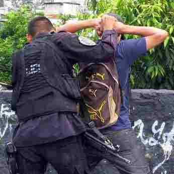 "Members of the Salvadoran police squad ""The Hawks"" search suspected gang members in San Salvador."