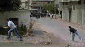 Men throw stones at riot police during clashes in the coastal town of Banias, Syria, on Friday.