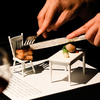 A diner cuts into pork belly on a chair at chef Bryon Brown's Sensorium, a 12-course tasting extravaganza.