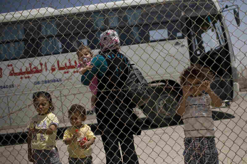 A Palestinian family waits to cross from the Gaza Strip into Egypt through the Rafah border crossing on Saturday.