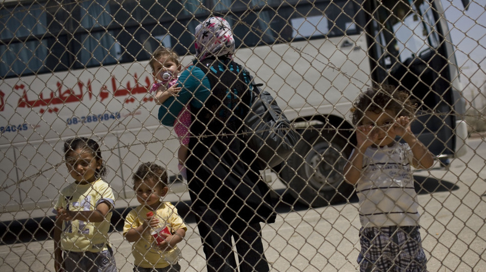 A Palestinian family waits to cross from the Gaza Strip into Egypt through the Rafah border crossing on Saturday. (AP)