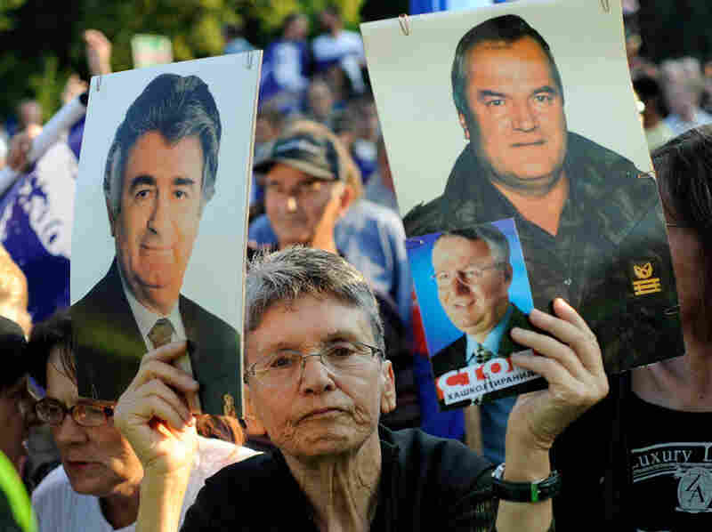 A protestor holds a picture of Bosnian Serb war crimes suspect Ratko  Mladic as she attends a demonstration in front of Serbian Parliament on  May 29, 2011 in Belgrade.