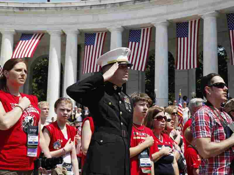 Members of Tragedy Assistant Program for Survivors (T.A.P.S.) stand during the  playing of the National Anthem at Arlington national Cemetery.
