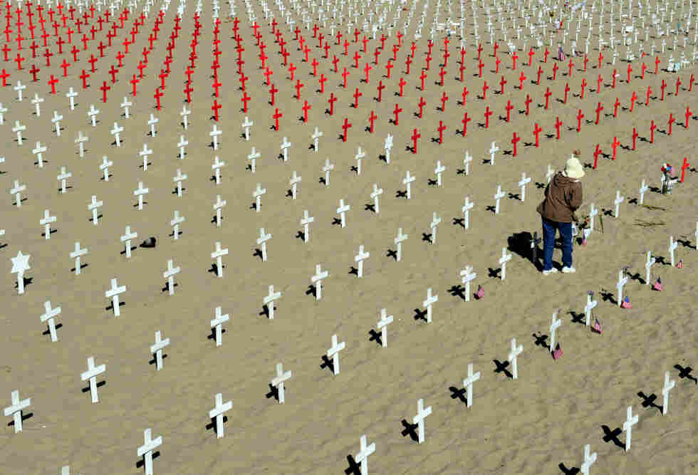 A woman walks among crosses at the Arlington West Memorial in Santa Monica, Calif., on Monday. Each red cross stands for 10 lost lives — a sign of the rising toll from the wars in Afghanistan and Iraq.