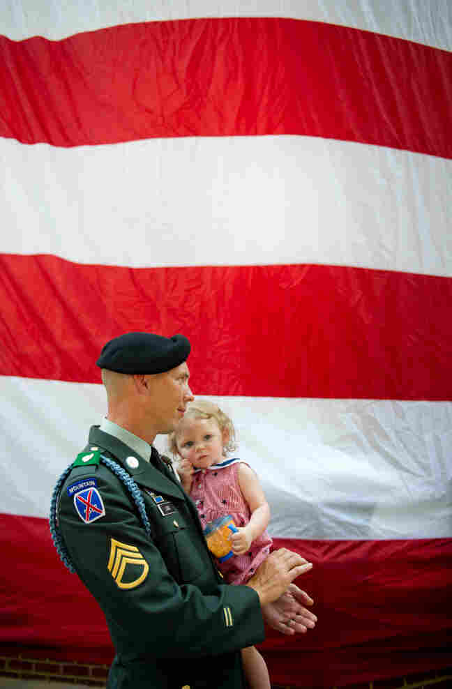 Jacob Long of the Georgia Army National Guard holds his 14-month-old daughter, Charlotte, during a Memorial Day ceremony in Roswell, Ga., on Monday.