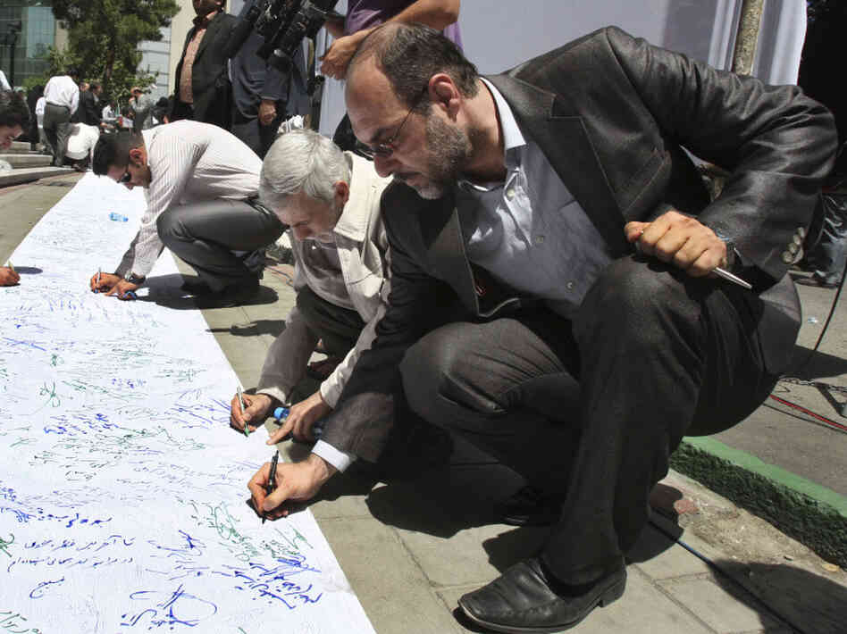 Iranian  demonstrators sign a scroll in symbolic support of the Bahraini opposition,  during a gathering at the Felestin  Square in central Tehran on May 23. Anti government protests have  spread across the Middle East this Spring. Some  hope they will lead to increased freedom and democracy in the region.