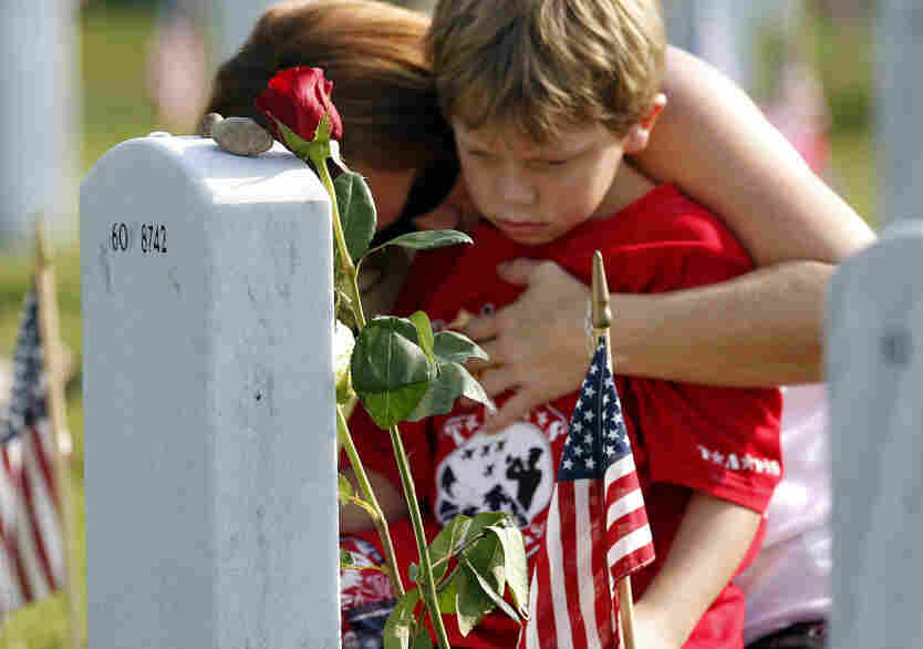 Trisha Lawton and her son, Caden, pray over the grave of husband and father Marine Capt. Garrett T. Lawton on Monday.