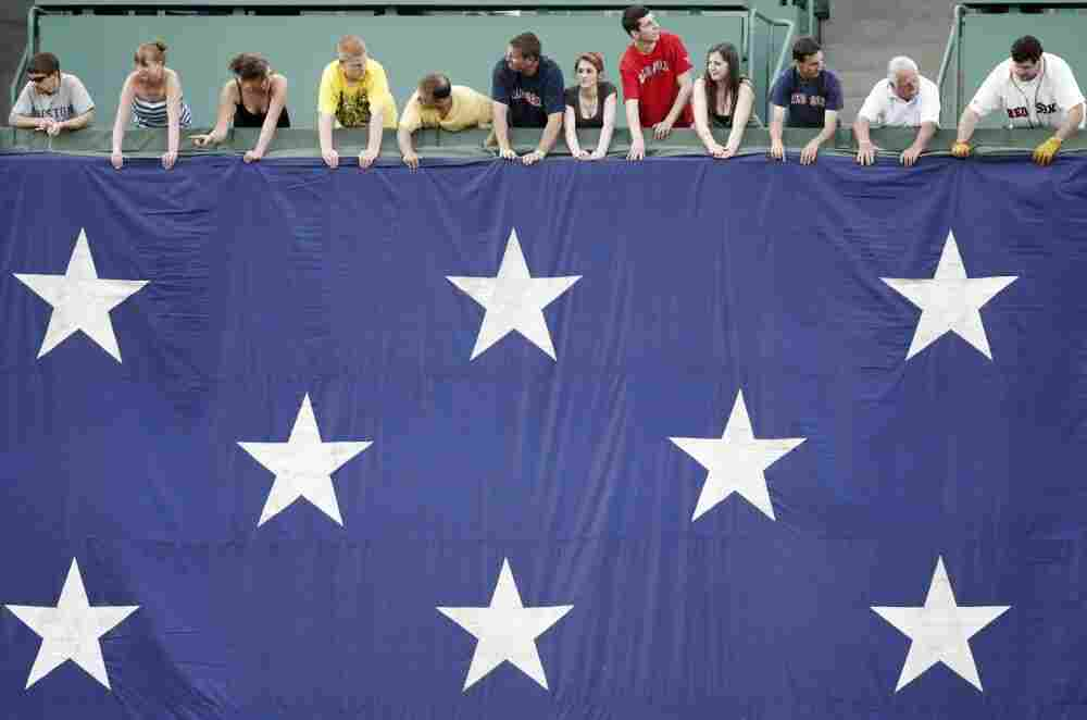 Boston Red Sox fans hold a large American flag before a game on Monday.