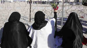 Bahraini protesters hold up flowers toward riot police near the Pearl Roundabout in February. On March 18, the government demolished the monument, which had become a prominent gathering place for opposition protesters.