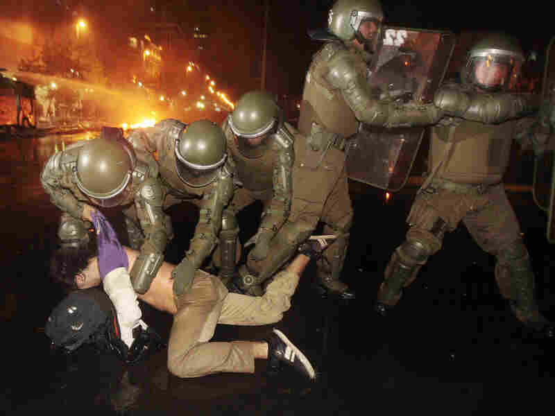 Police officers detain a demonstrator during clashes after a protest in front of La Moneda government palace in Santiago, Chile, May 20. The protest was against a $7 billion project by the multinational consortium HidroAysen to dam two of the world's wildest rivers in Patagonia for electricity.