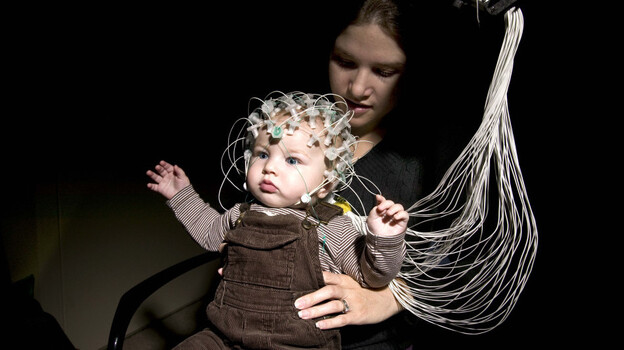 An infant and his mother demonstrate electroencephalography, or EEG, technology at Children's Hospital Boston. The technology could help detect the risk of autism in infants. (Courtesy of Michael Carroll)