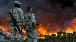 Two soldiers watch 134 tons of marijuana seized by the Mexican Army burn in the border town of Tijuana, Mexico, in October 2010.