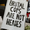 """At a rally in Chicago in 2004, demonstrators display a sign that reads 'Brutal Cops Are Not Heroes."""""""