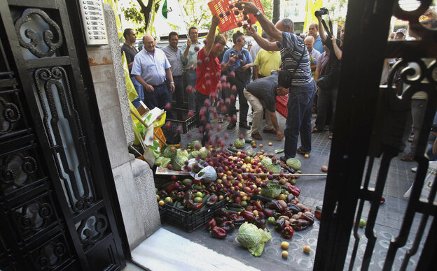 Protesting farmers dump some 700 pounds of fruit and vegetables outside the German consulate in Valencia, Spain.