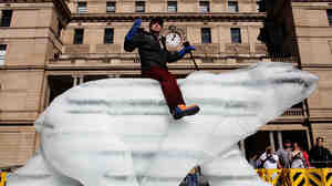 """The """"Sydney Ice Bear"""" on Friday in Sydney, Australia. The bear was carved by British artist Mark Coreth from a 10-ton block of ice. The public will be welcomed to touch the bear, leaving imprints that will begin the melting process and act as a metaphor for how humans affect the environment."""
