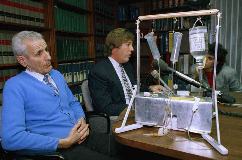 Kevorkian (left), then 62, listens as his attorney talks with reporters, Feb. 6, 1991. Pictured on the table is the machine he used to inject lethal drugs into 130 people.