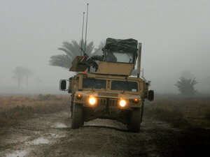 A U.S. soldier from the 6th Squadron, 8th Cavalry Regiment, mans a machine  gun on top of a Humvee as it navigates a muddy road on the southern outskirts of  Baghdad.
