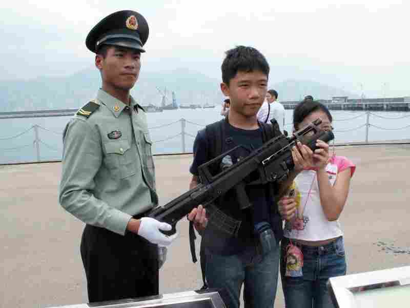 China's army bases open their doors every year to try to build their image among Hong Kong's population. Troops pose for pictures and allow children to learn about their weapons.
