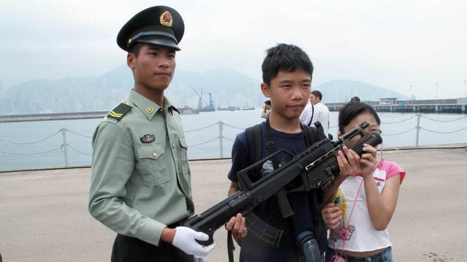 China's army bases open their doors every year to try to build their image among Hong Kong's population. Troops pose for pictures and allow children to learn about their weapons. (NPR)