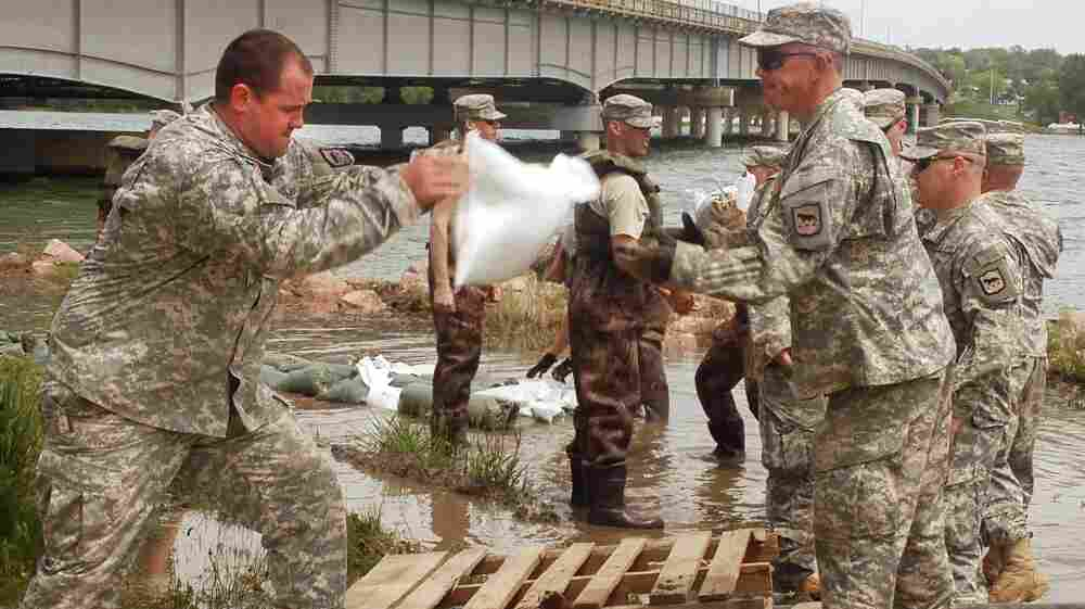 South Dakota National Guard members from Watertown, S.D., stack sandbags to prevent floodwaters from the rising Missouri River from reaching an electrical box in Ft. Pierre on Thursday.