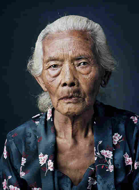 Kasinem, born 1931, Kemuning, Central JavaAt age 13, Kasinem received the Japanese name 'Kanaku' and had to service three or four men every day. In the brothel, where another 30 women were kept, too, each had her own room. Years later she married and started a family of six children. She now lives with grandchildren and great-grandchildren and works in the rice fields behind the house.