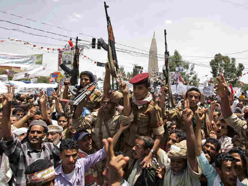 Yemeni army soldiers, lifted by anti-government protesters, chant slogans and hold up their rifles as they celebrate President Ali Abdullah Saleh's departure to Saudi Arabia, in Sanaa, Yemen, on Sunday.