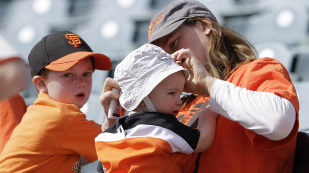 Erica Fortescue of San Francisco puts sunscreen and a hat on 11-month-old Nico Fortescue as her brother Theo, 4, looks on during a March spring training baseball game in Phoenix.