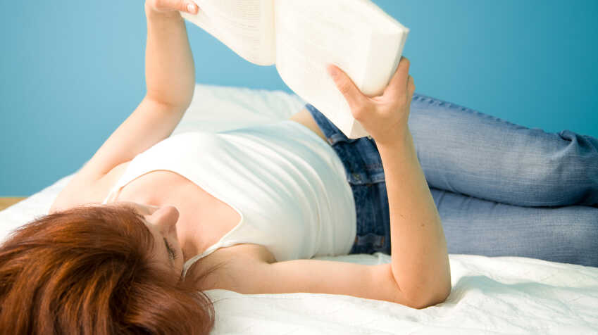 A girl lies on her back reading a book.