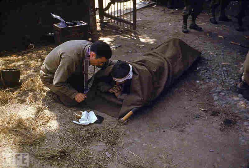 An American Army chaplain kneels next to a wounded soldier in order to administer the Eucharist and last rites.