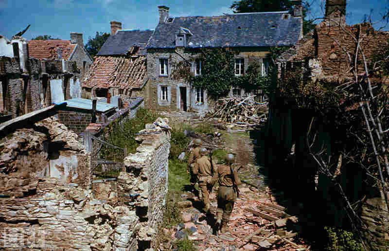 Soldiers search ruined homes in western France after D-Day.