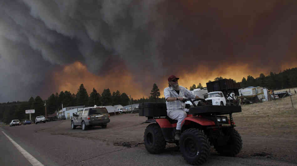 Robert Joseph, 64, rides his ATV as smoke plumes from the Wallow Fire fill the sky in Luna, N.M., on Monday.