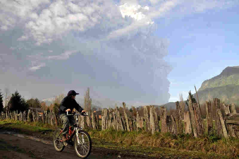 A boy on a bicycle pauses Monday to look at a plume of smoke and ash emerging from the volcano.