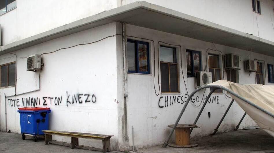 """Graffiti at the smaller Greek pier at Piraeus says """"Chinese go home."""" Greece's dockworkers unions were opposed to the Chinese involvement at Piraeus, although among the general public, the mood was more positive. (NPR)"""