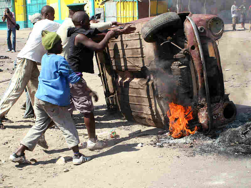 Last September, Mozambican protesters overturned a burning car in Maputo. Police patrolled the streets of the tense capital after President Armando Guebuza called for calm following protests over food and fuel prices.