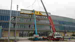 Construction crews hang the Livestrong banner on the new stadium. Investors plan to donate up to $8 million in revenues to the Livestrong foundation over the next five years.