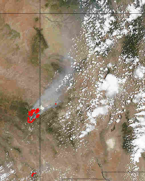 This satellite image from NASA's MODIS Land Rapid Response Team shows the fires in red, along the Arizona border with New Mexico (the line just to the right of the red marks that pinpoint the flames), and the smoke billowing to the northeast. It was taken Monday.