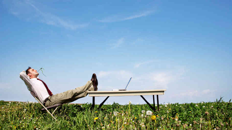 A man relaxes with a computer in front of him.