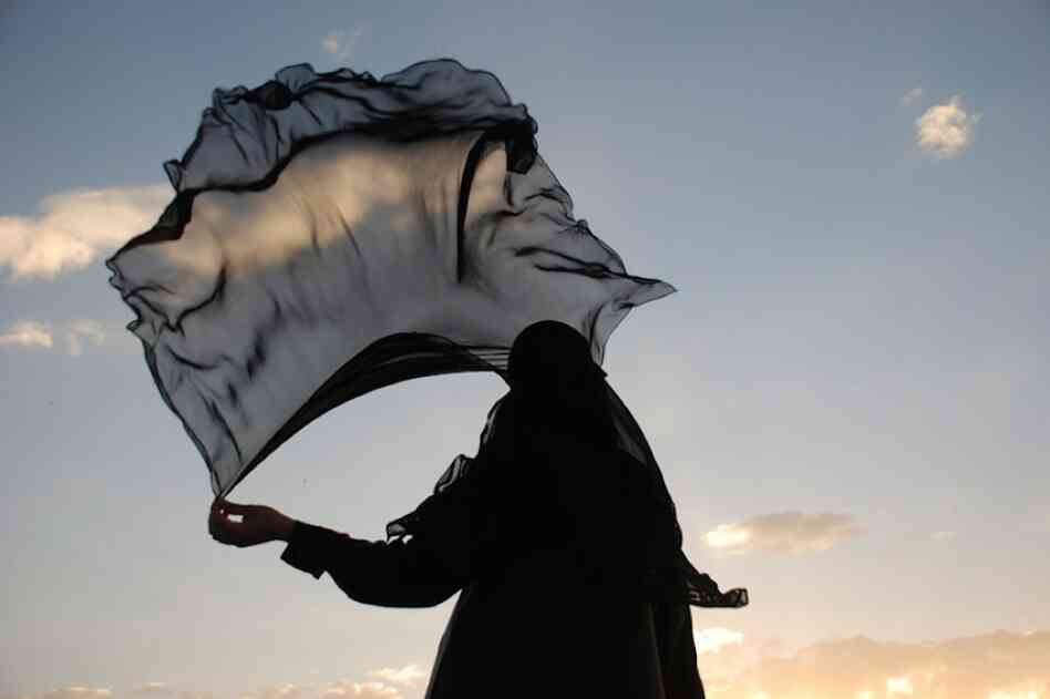 A woman in Yemen holds her veil. Photojournalist Amira Al-Sharif is undertaking a project that compares and contrasts the lives of young women in Yemen and the United States.