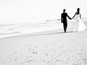 A bride and groom stroll at the beach.
