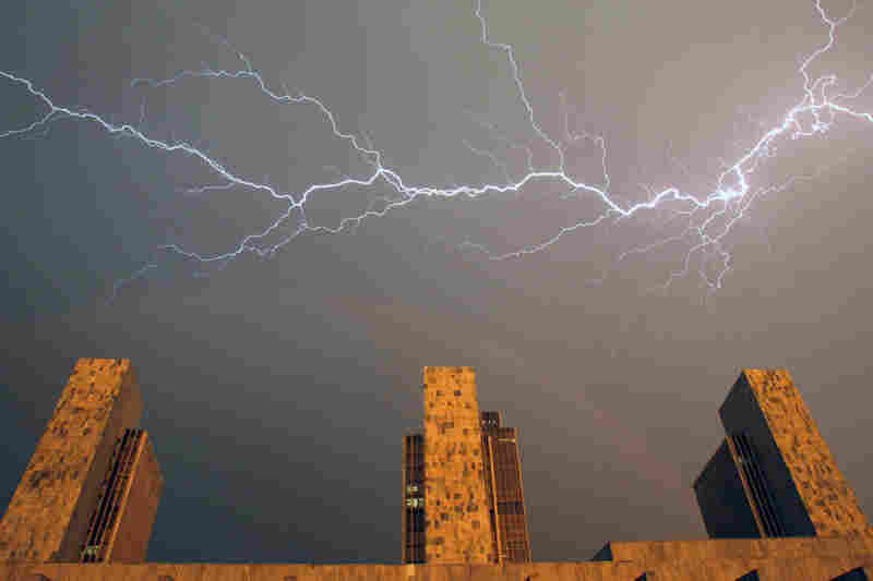 Heat lightning and a rainbow stretch across the sky over state agency buildings at the Empire State Plaza in Albany, N.Y. The mercury climbed into the 90s across half the country Wednesday.