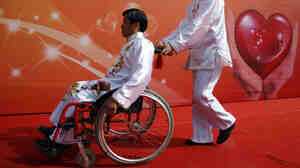 A man pushes a friend in a wheelchair following an event in Beijing to raise awareness of accessibility issues for the disabled.